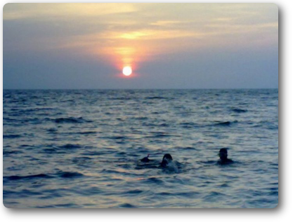 swimming with Sunset over the ocean in front of the resort